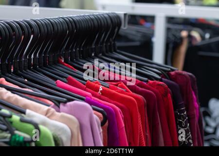 Mucha ropa femenina de colores en las perchas. Nuevo concepto de colección de ropa
