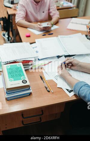 Un maestro anónimo conduce una lección para los estudiantes en el aula. Libros de literatura en ruso para la escuela secundaria sobre una mesa de madera.
