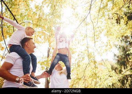 La madre y el papá mantienen a los niños en los hombros y en las manos. Alegre familia joven tienen un paseo juntos en un parque de otoño
