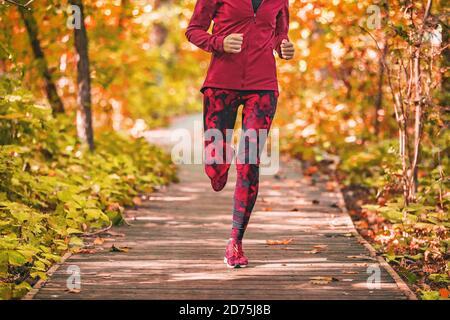 Correr camino mujer corriendo en el bosque parque naturaleza al aire libre ejercicio físico en el paseo marítimo en otoño follaje con rojo activewear ropa de conjunto. Chica