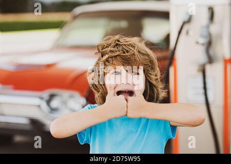 Un niño con un coche retro en la gasolinera Vintage pulgares para arriba.