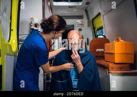 Un médico joven con estetoscopio está cuidando a su paciente herido en un auto de ambulancia.