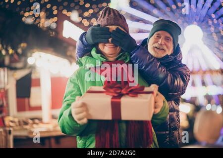 Foto de dos personas jubilados amantes pareja palmas cubrir los ojos abuelo preparar caja de regalo abuela mantener caja blanca rojo lazo ropa abrigo bufanda rojo ropa de cabeza x-mas