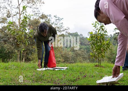 un par de mujeres recogiendo basura de un bosque y.. poniéndolo en una bolsa de tela