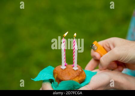 Mano con un encendedor para encender las velas muffins de arándanos sobre fondo verde. Quemando cuatro velas en la celebración del cumpleaños.