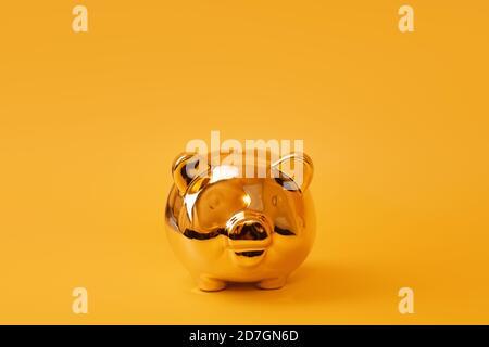 Banco piggy dorado sobre fondo amarillo. Caja de oro. Dinero en bruto, ahorro de dinero, moneybox, finanzas e inversiones concepto. Espacio libre para texto
