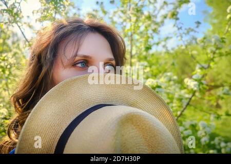 Una mujer cubre su rostro con un sombrero en un parque de primavera