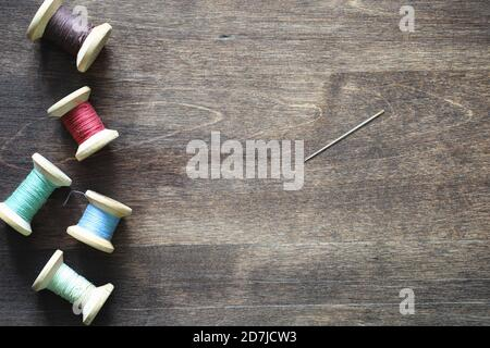 Hilo de Coser sobre un fondo de madera. Conjunto de subprocesos en bobinas de estilo retro. Vintage accesorios para coser sobre la mesa.