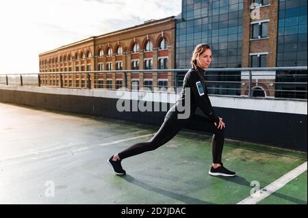 Mujer atleta estirando las piernas en la azotea contra los edificios de la ciudad