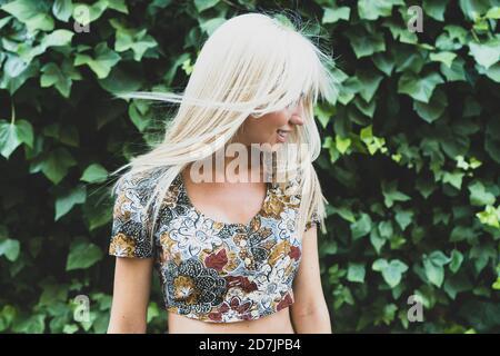 Sonriente mujer joven sacudiendo el cabello mientras está de pie contra las plantas en parque