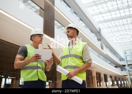 Retrato en ángulo bajo de dos contratistas profesionales del edificio que usan tabletas digitales mientras están de pie en el lugar de construcción en el edificio de oficinas, espacio de copia