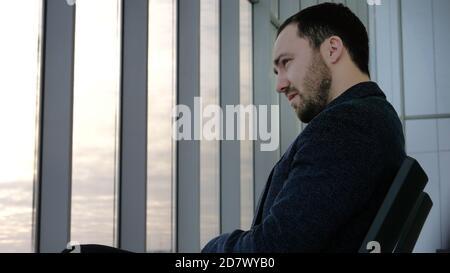 Hombre cansado esperando un vuelo retrasado.