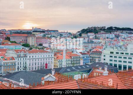 Vista de hermosas y coloridas casas desde arriba durante el amanecer con el cielo naranja y rosa en Lisboa, Portugal. Foto de stock