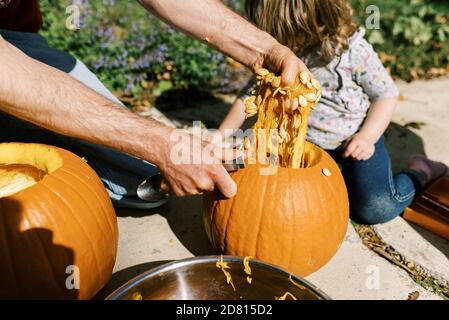 Pequeña niña tallando calabazas para halloween con su papá