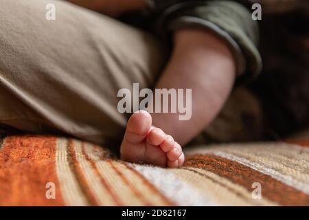 Enfoque selectivo de pequeños pies y dedos pequeños del recién nacido bebé niño que se relaja en el regazo de los padres mientras se sienta sofá en casa