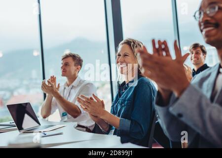 Grupo de hombres y mujeres profesionales de negocios que se aferran a la conferencia. La audiencia aplaude después de un seminario exitoso.