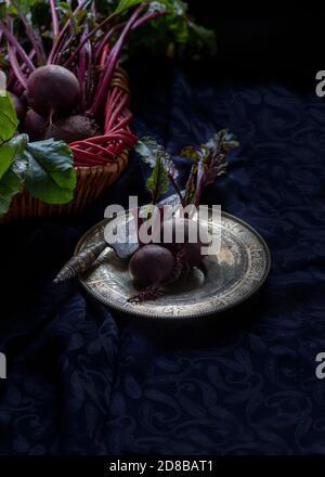 Composición con remolacha fresca madura dispuesta sobre la mesa con cosecha plato rústico y cuchillo Foto de stock