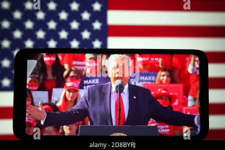 En esta ilustración, el presidente estadounidense Donald Trump vio hablar durante un mitin de campaña en el aeropuerto Phoenix Goodyear en Goodyear, Arizona, en una emisión en directo que se mostraba en una pantalla de teléfono inteligente. Foto de stock