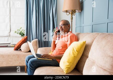 retrato de un hombre mayor indio asiático moderno utilizando un portátil en mientras está sentado en el sofá y hablando en el móvil o smartphone