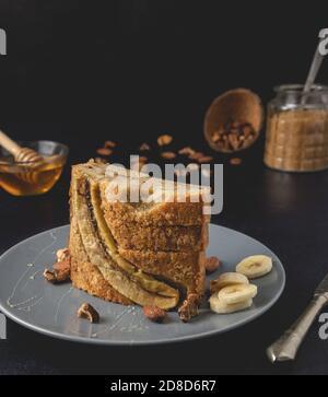 Pan de nuez de plátano casero pan pan de pan colocado en el plato. Vista frontal, primer plano. Una textura de pan suave y apetitosa, con aroma de nuez y miel triturada.