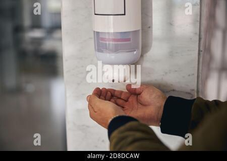 Macho desinfectando sus manos con gel a base de alcohol
