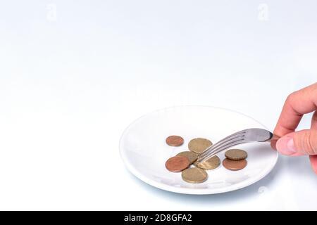 La mano sostiene un tenedor con monedas de céntimo de euro en un plato blanco sobre un fondo blanco, primer plano, espacio de copia