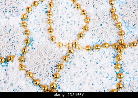 Vista de cerca de cuentas doradas con copos de nieve decorativos y nieve artificial sobre fondo azul, concepto de año nuevo