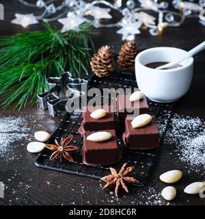Marzipancubes con helado de chocolate en una rejilla de enfriamiento negro, decorado con ramas de pino, bastones de canela y estrellas de anís, conos de abeto, junto a ella un arco