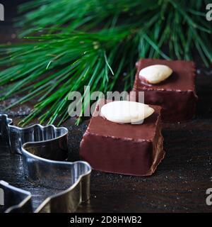 Cubos de mazapancuta con chocolate en una rejilla de enfriamiento negro, decorado con ramas de pino, bastones de canela y estrellas de anís, conos de abeto