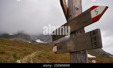 Vista de primer plano de letrero de madera y marcado de senderos que muestra las direcciones a Rescher Alm y Piz Lad en el sur de Tirol con montañas cubiertas de nubes.
