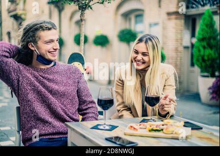 Pareja bebiendo vino tinto en el bar con máscaras de cara abierta En el tiempo de coronavirus - Nuevo concepto normal - enfoque en mujeres