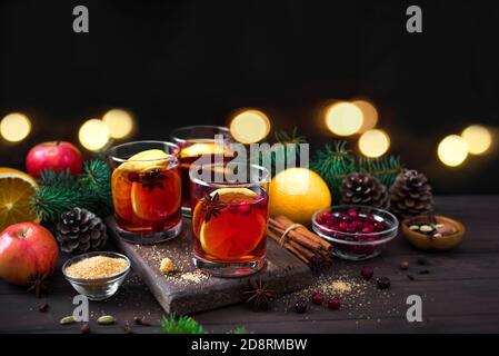 Vino tinto de Navidad con especias y naranjas sobre mesa rústica de madera. Bebida caliente tradicional para las vacaciones de Navidad e invierno.