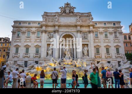 Ciudad de Roma, Italia, Fontana de Trevi (Fontana di Trevi) al atardecer y grupo de personas, los turistas disfrutan de la vista de un monumento mundialmente famoso