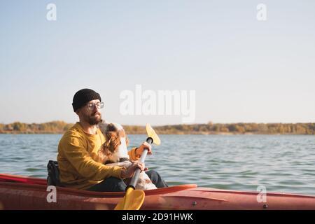 Hombre con un perro en una canoa en el lago. Joven hombre con nalgiel en un kayak en barco de fila, tiempo libre activo con mascotas, compañía, perros de aventura