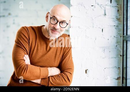 Retrato de hombre curioso con barba y gafas de pie en la pared y mirando la cámara.