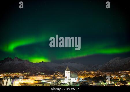 Bailando luces polares verdes sobre la ciudad Svolvaer en el Lofoten islas en Noruega por la noche en invierno con nieve
