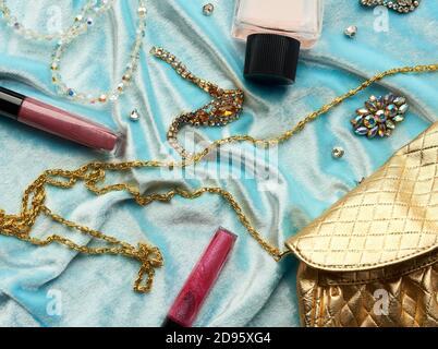 bolso de oro, brillo de labios y cuentas sobre un fondo azul, vista superior.