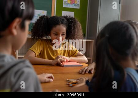 Una niña seria de la escuela afroamericana mirando a los niños en el aula, jugando un juego, desafiando, aprendiendo, contando. Niña de la escuela con las manos en la mesa concentrándose durante el desafío