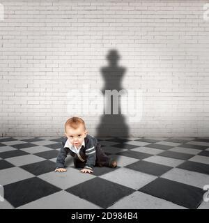 niño pequeño con sombra de rey en un piso a cuadros