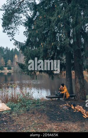 Un hombre se sienta junto al lago en un banco, junto a un árbol.