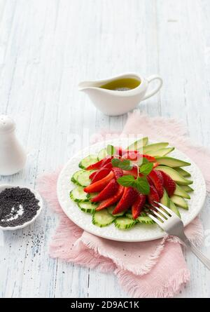 Ensalada vegana de fresa, pepino y aguacate con semillas de amapola, aderezo de aceite y menta. Alimentos frescos, saludables y dietéticos. En un plato blanco y en un blu