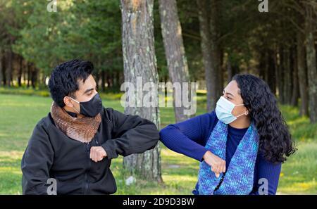 El joven vestido de negro y con una máscara saluda con su codo a una mujer vestida de azul una máscara que está sentada en un banco del parque Foto de stock
