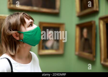 Retrato de la mujer con máscara de protección en el museo
