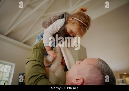 Un padre joven que levanta al niño en el aire mientras juega en casa