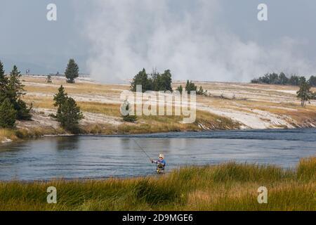 Un pescador de moscas en el Río Firehole en el Parque Nacional Yellowstone en Wyoming. El vapor se eleva desde la cuenca del Geyser Midway detrás.