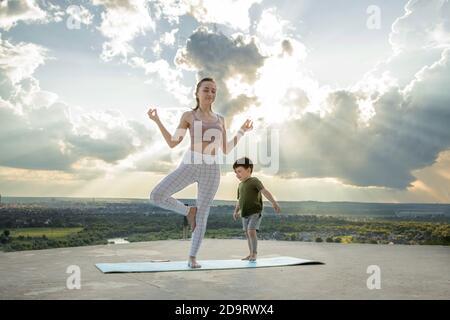 Madre e hijo haciendo ejercicio en el balcón en el fondo de una ciudad durante el amanecer o el atardecer, concepto de un estilo de vida saludable