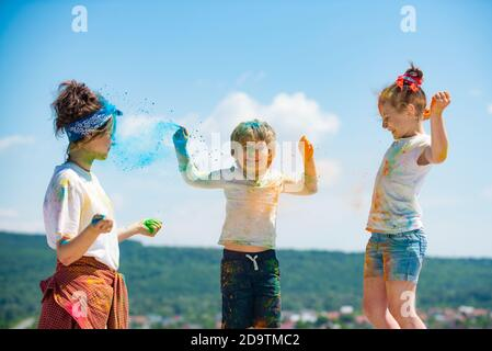 Niños brillantes y felices jugando con polvo de colores.