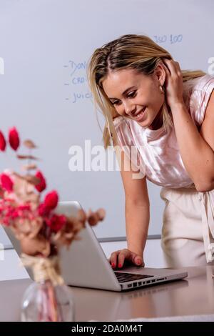 Encantada mujer independiente sentada en la mesa con el portátil y trabajando de forma remota en casa