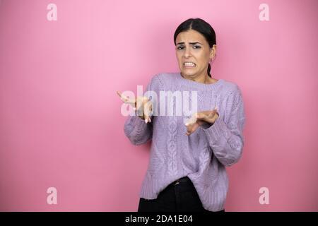 Hermosa mujer con un suéter violeta casual sobre fondo rosa expresión disgustada, disgustado y temeroso haciendo cara de disgusto porque aversión