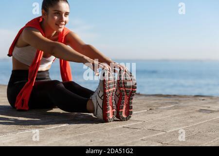 Tiro al aire libre de sonriente entrenamiento deportivo seguro cerca del mar. Mujer de fitness sentada en el muelle de madera y estirando las piernas